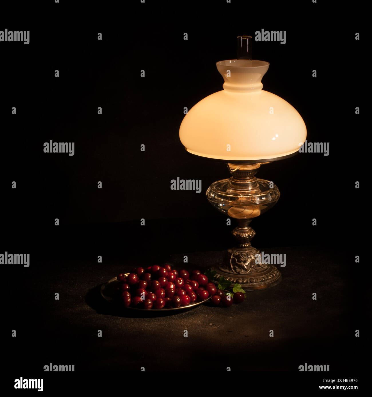 The Kerosene lamp and a plate cherries as a still life with a black background - Stock Image