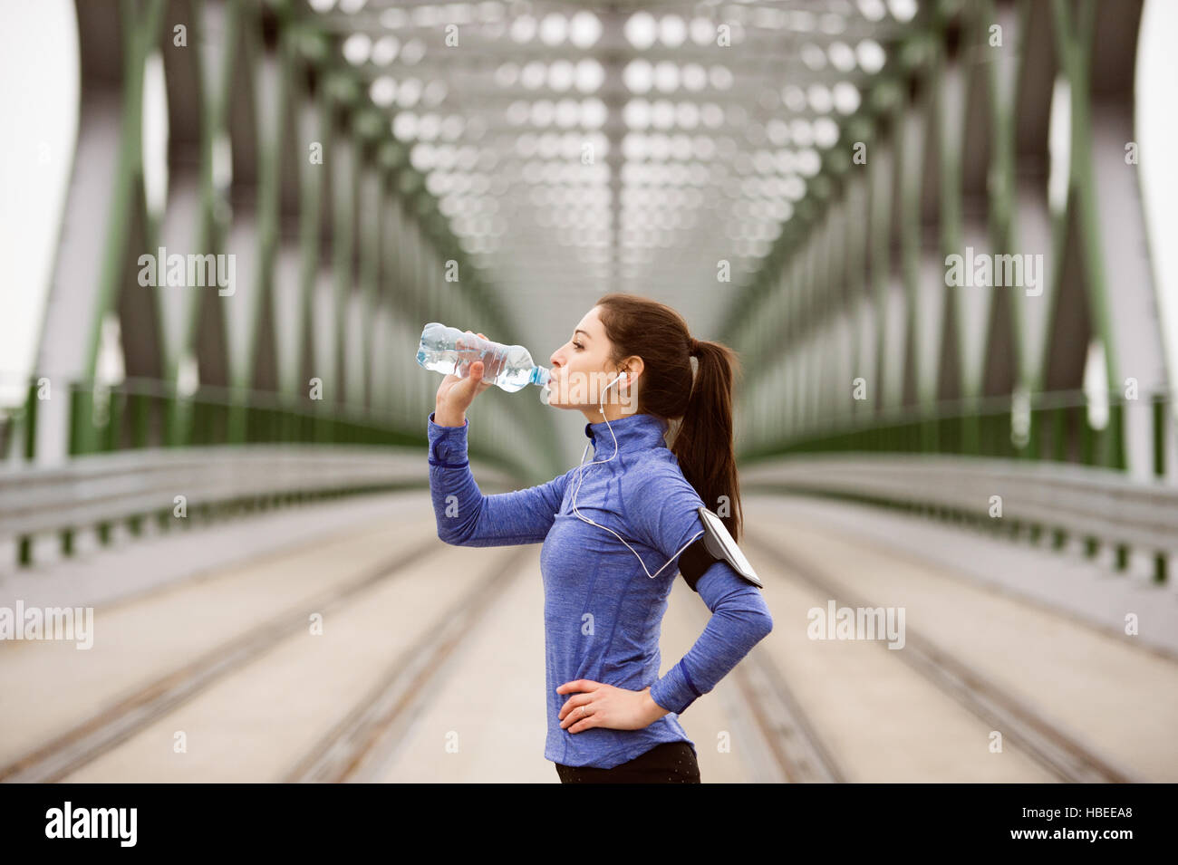 Young runner resting, drinking water on green steel bridge - Stock Image