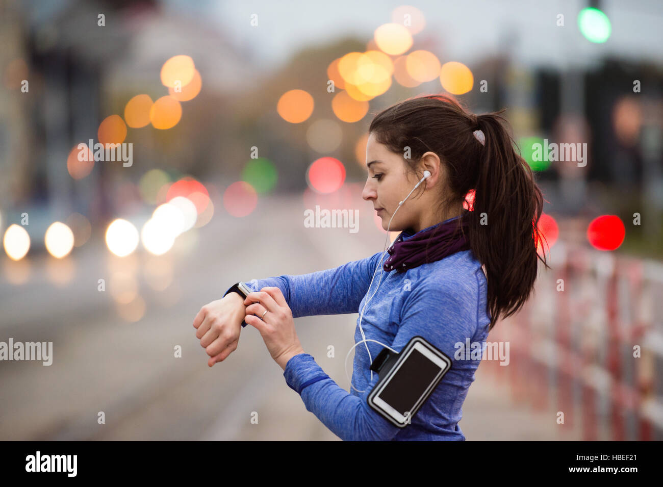 Young woman in blue sweatshirt running in the city - Stock Image