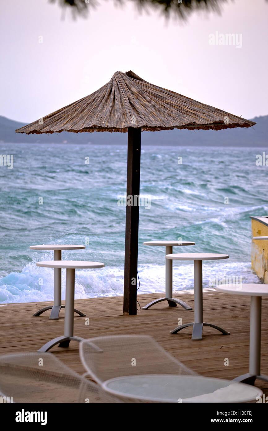 Beach bar parasol by rough sea vertical view, Zadar, Croatia - Stock Image