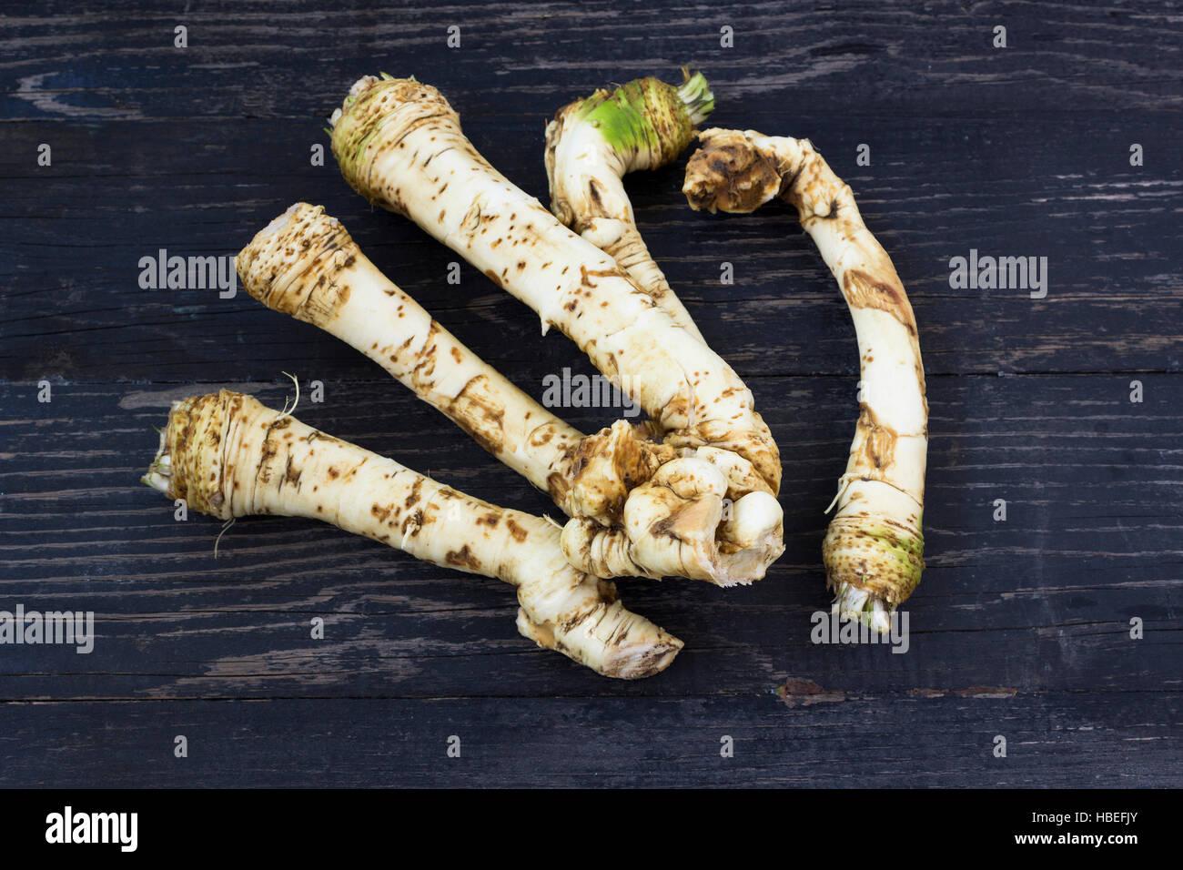 Fresh horseradish roots on wooden background - Stock Image