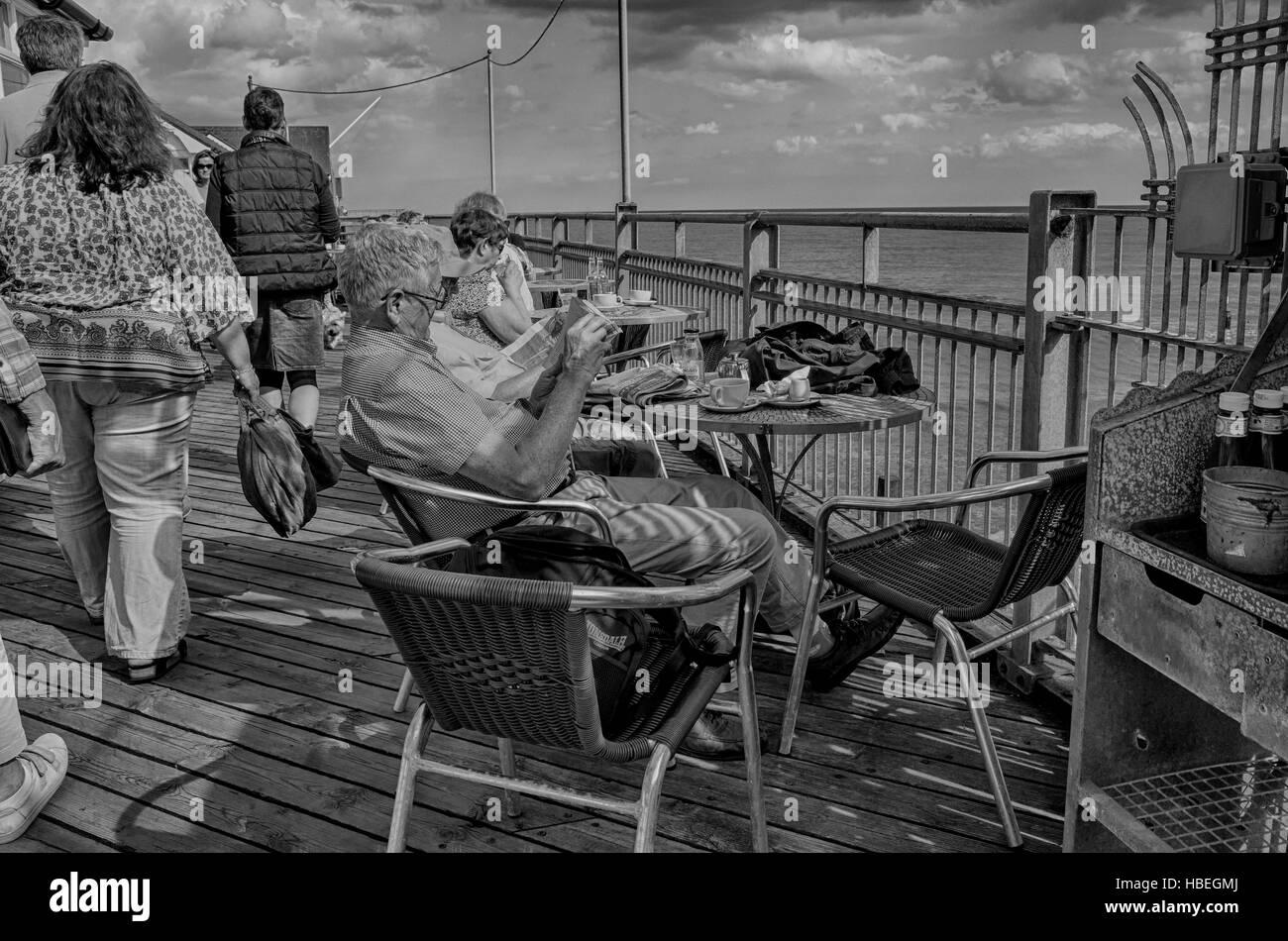 Southwold, England. Elderly people enjoying the sunny weather sitting along Southwold pier drinking tea and reading Stock Photo