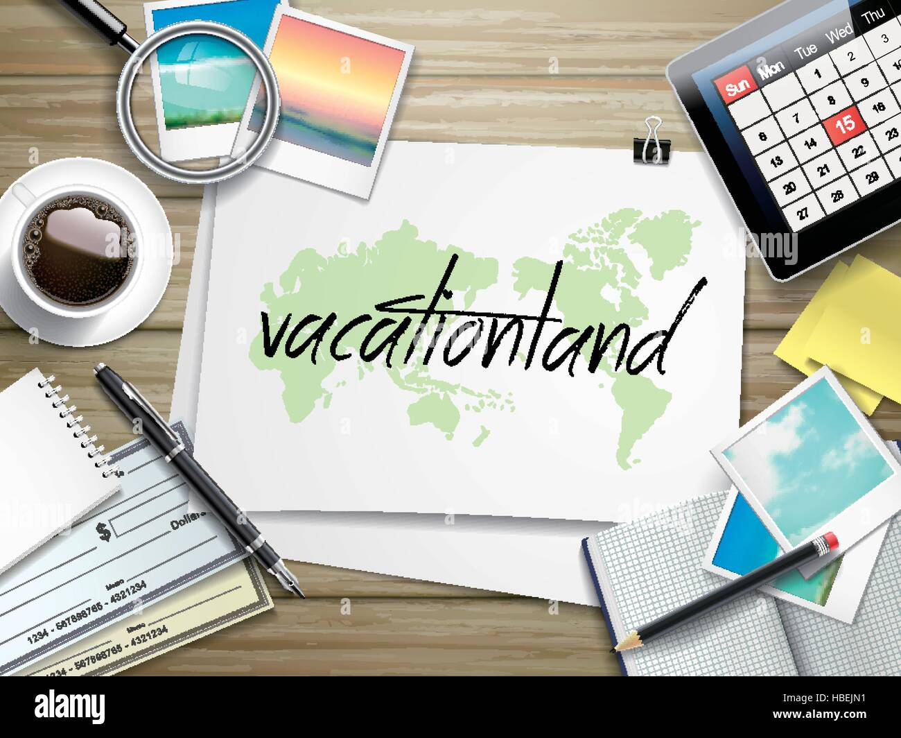 top view of travel items on wooden table with vacationland word written on paper - Stock Image