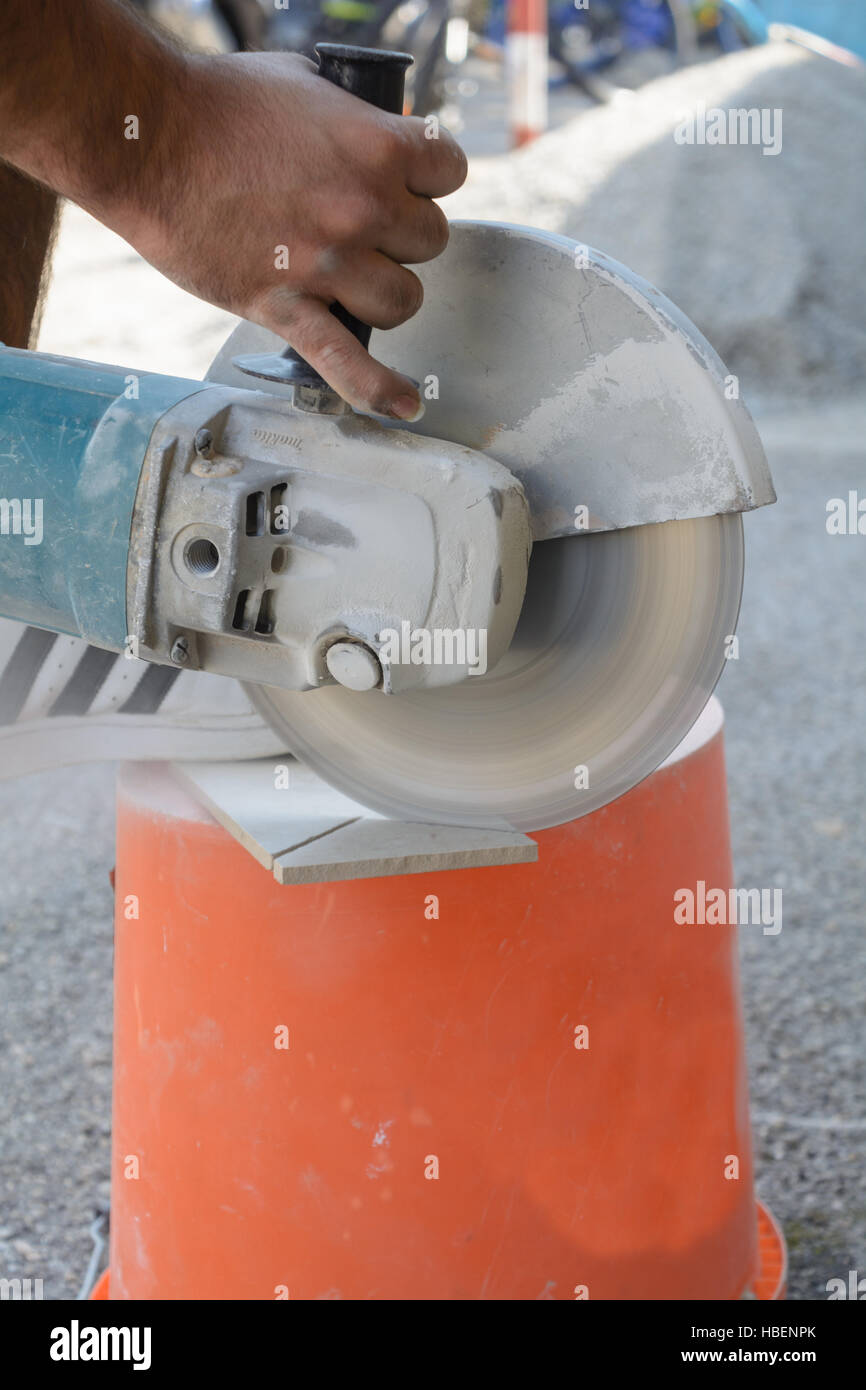 Skilled worker cuts tiles with angle grinder - Stock Image