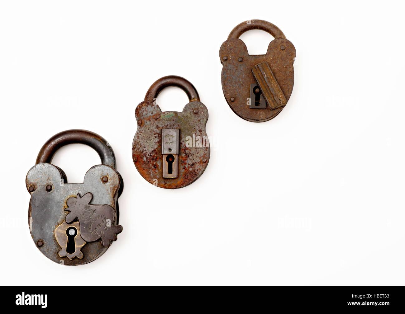 Three old padlocks on a white background - Stock Image