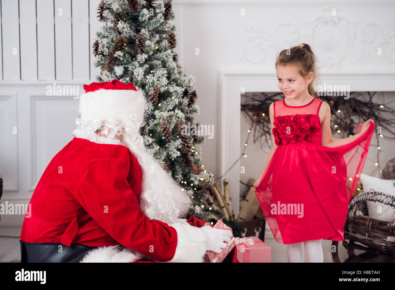 Santa Claus and children opening presents at fireplace. Kids father in costume wearing beard open Christmas gifts. Stock Photo