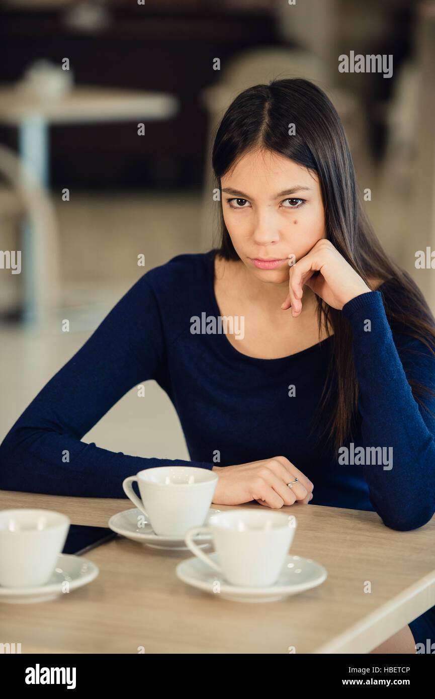 Angry young woman with crossed arms at cafe - Stock Image