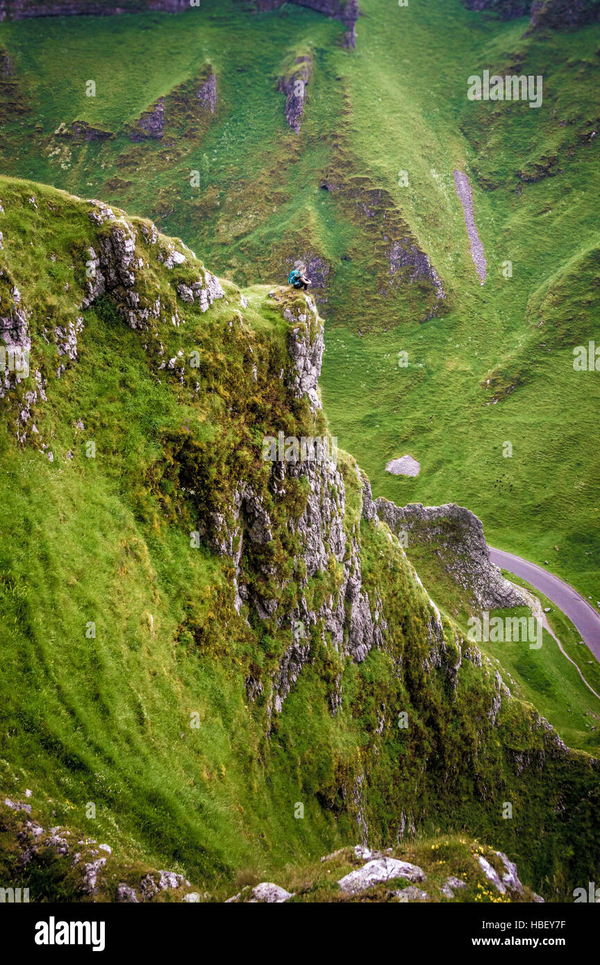 Female on rocky outcrop with road below, Peak District, Derbyshire, UK. - Stock Image