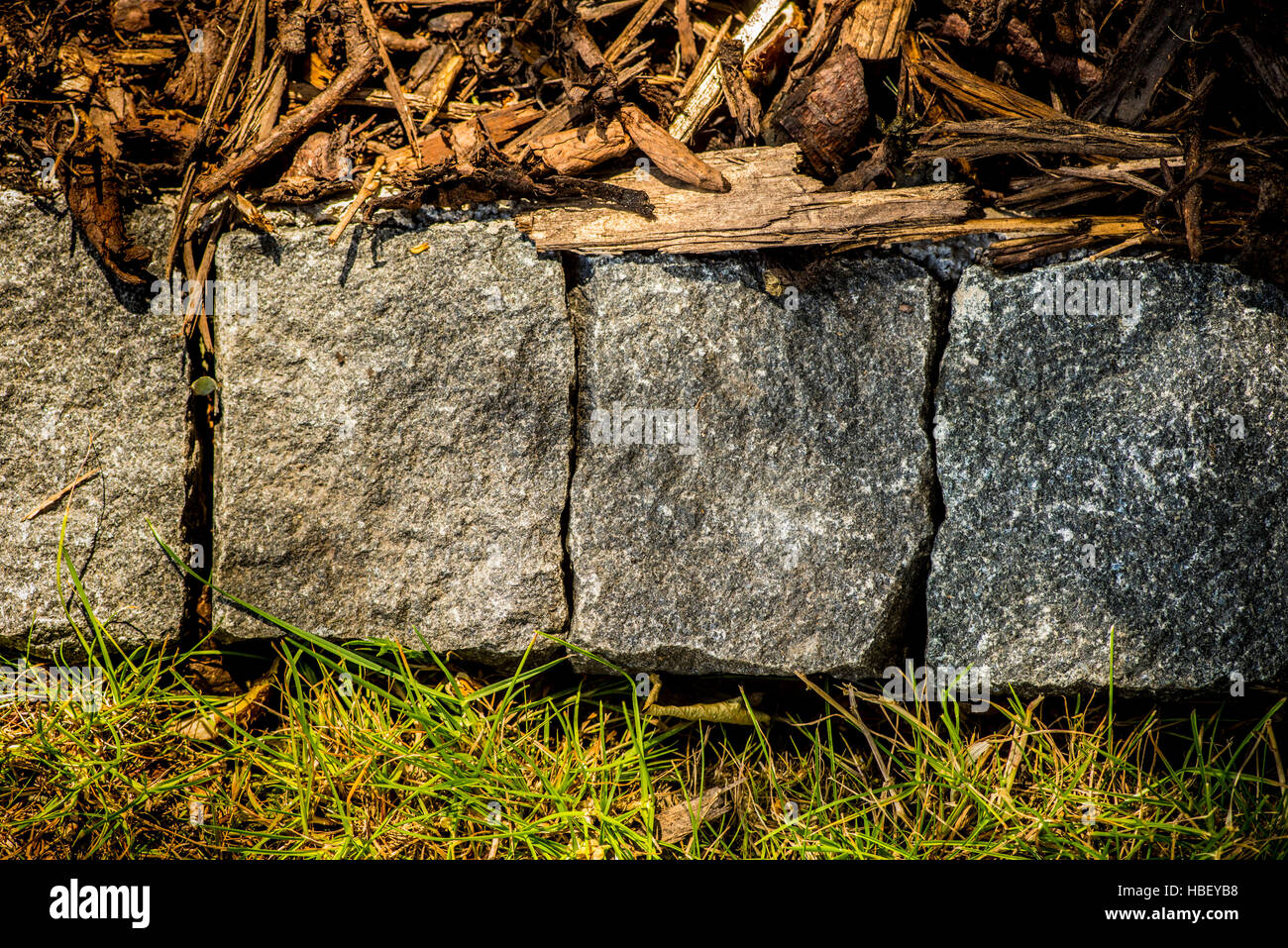 boundary between lawn and flower bed edged with block pavers - Stock Image