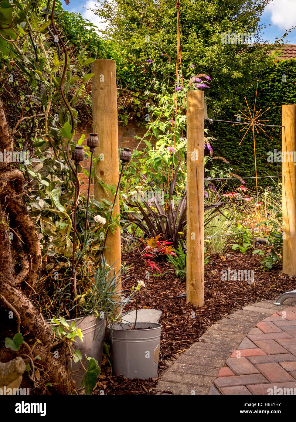 Garden areas divided using wooden stakes to create outdoor rooms in modern contemporary design - Stock Image