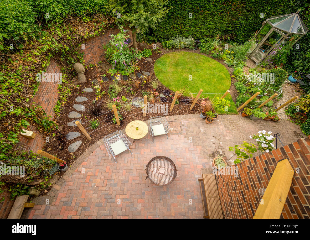 Modern garden seen from above with circular lawn and block paved patio - Stock Image