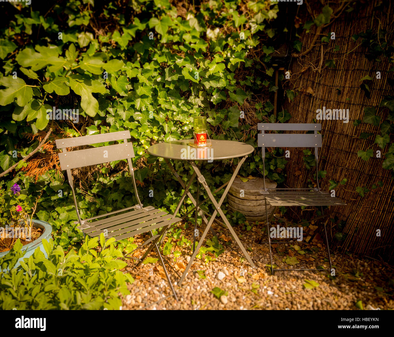 Bistro seating area in UK garden with table and two chairs - Stock Image