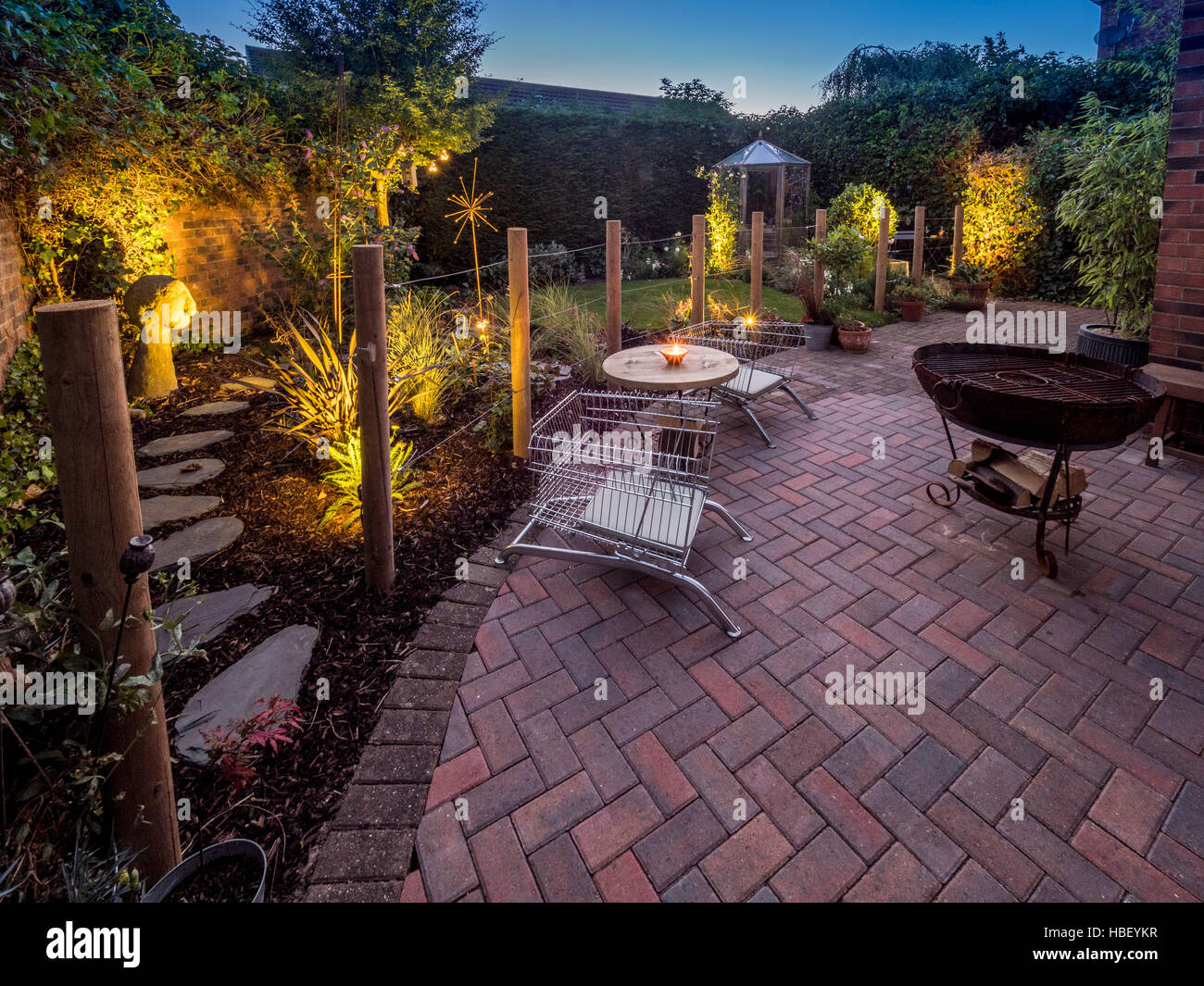 Modern garden design at dusk with contemporary wire shopping trolley chairs for seating and large Kadai firebowl Stock Photo