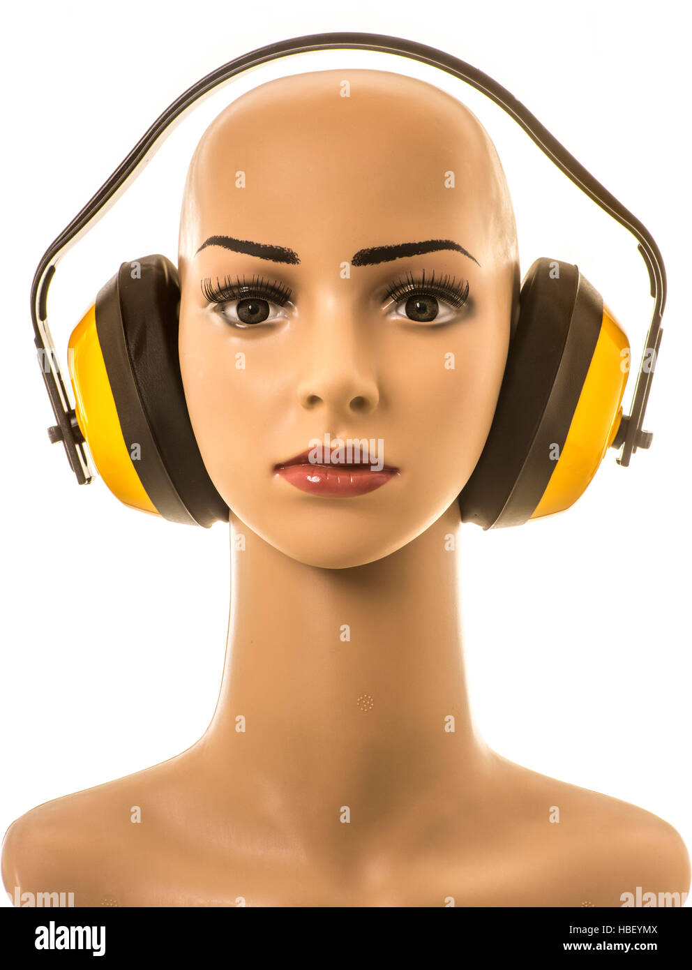 Mannequin wearing yellow ear defenders for hearing protection. - Stock Image