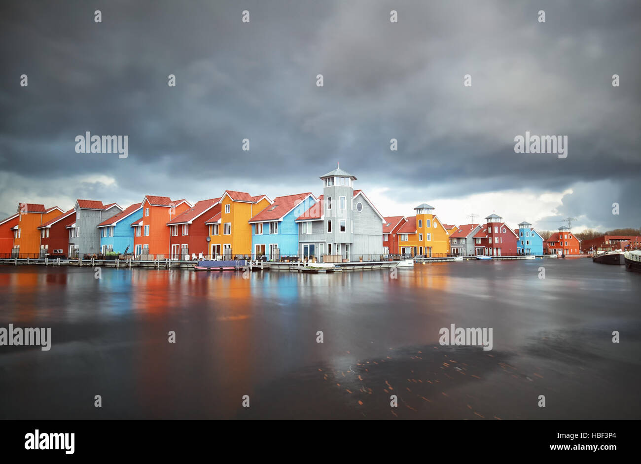 colorful buildings on water during storm - Stock Image
