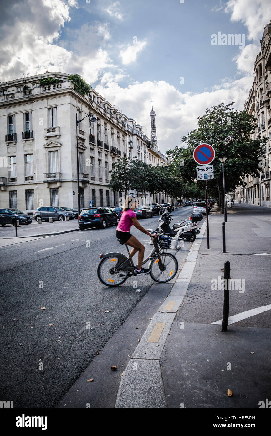 young woman visiting Paris with bicycle Stock Photo