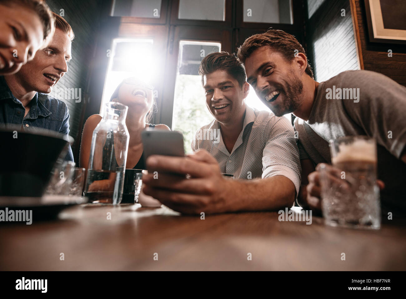 Group of friends sitting together in a cafe looking at smart phone and smiling. Young guy showing something to his - Stock Image