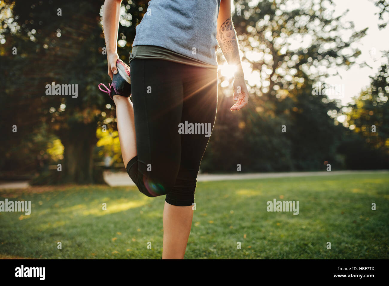 Cropped shot of fitness woman stretching legs. Female model exercising in the morning at city park. - Stock Image