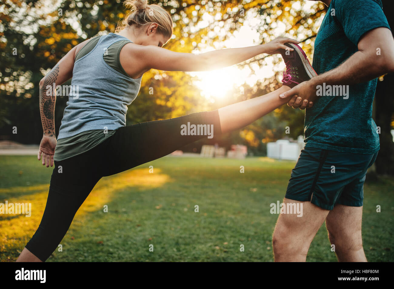 Male coach helping young woman exercising in park. Trainer helping woman in leg stretching workout. Stock Photo