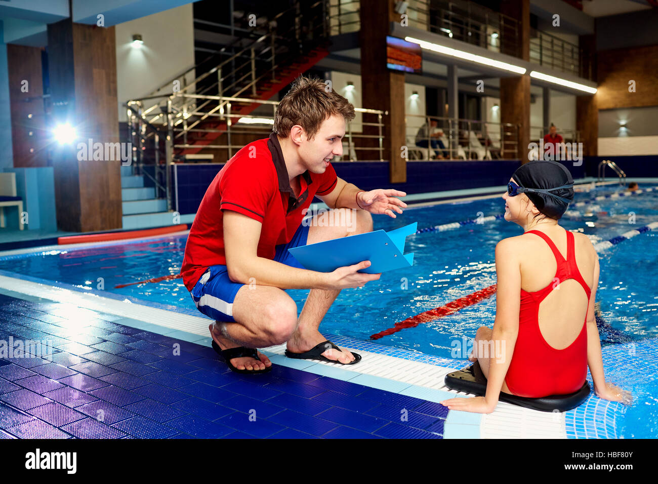 Coach,tranier to swimmer girl at the pool discussing with athlet - Stock Image