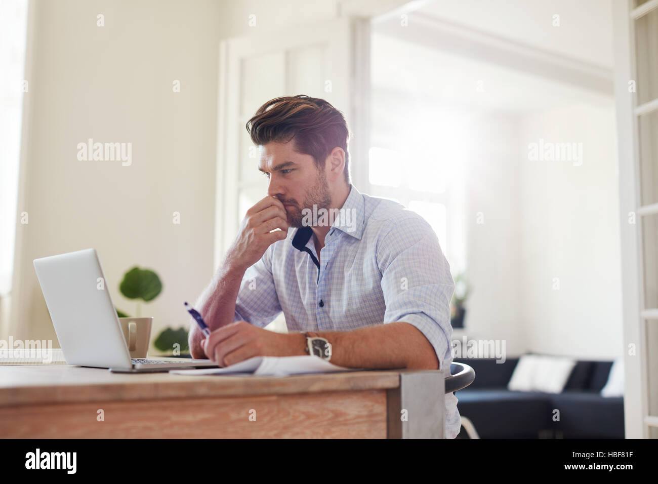 Side view shot of pensive young man sitting at home and working on laptop. Caucasian male working from home office. - Stock Image