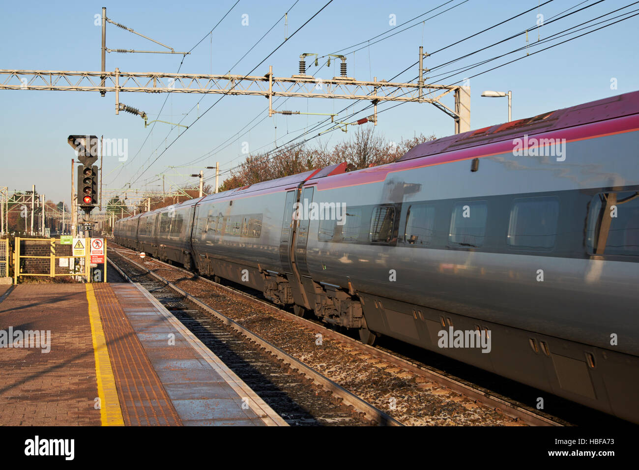 virgin trains intercity train speeding past overhead electricity wires on rail track at liverpool south parkway - Stock Image