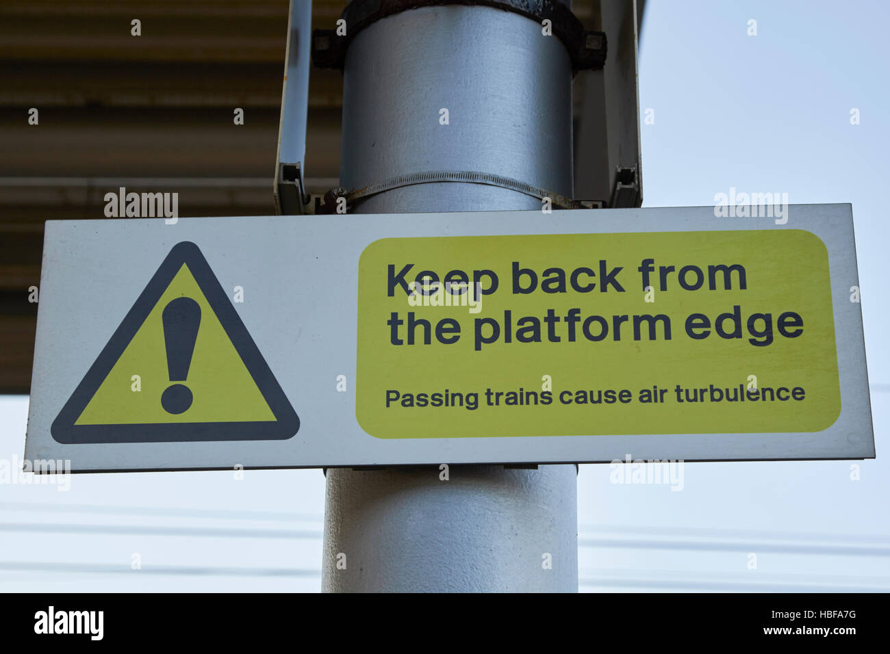 train station platform warning sign keep back from platform edge passing trains cause air turbulence - Stock Image