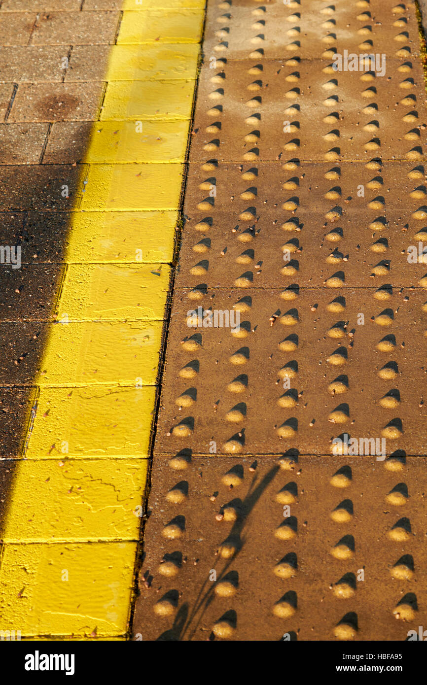 yellow lines and textured area of edge of train platform in the uk - Stock Image