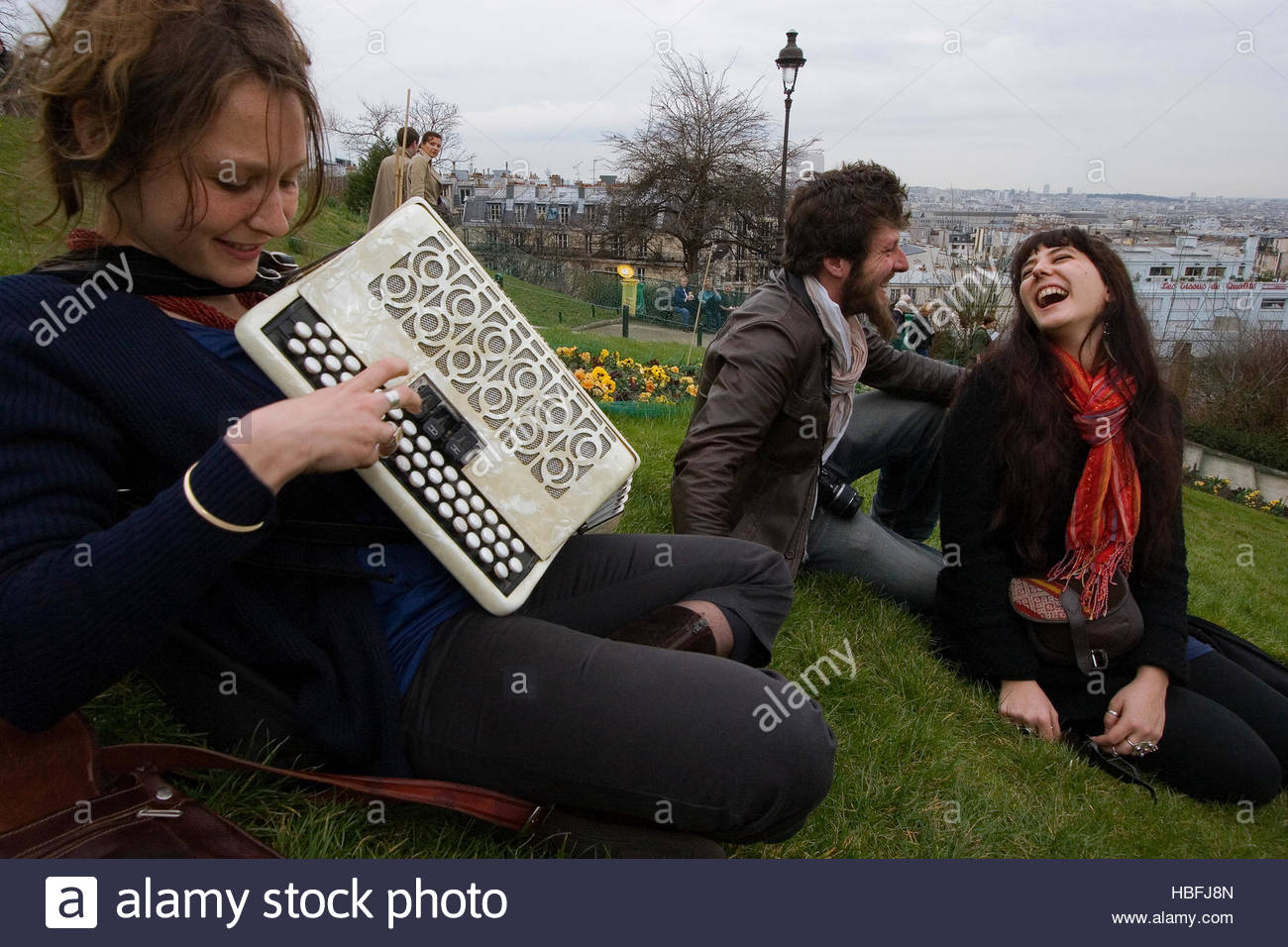 Friends meet on a lawn below Sacre Coeur for accordion music and laughs. - Stock Image