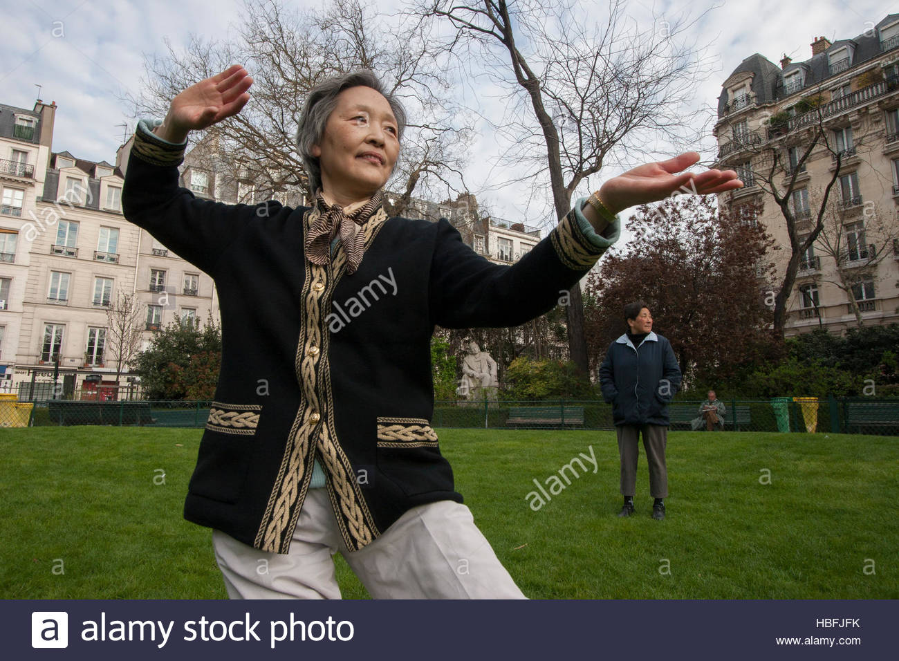 Members of the Asian community practice Tai Chi in Square du Temple. - Stock Image