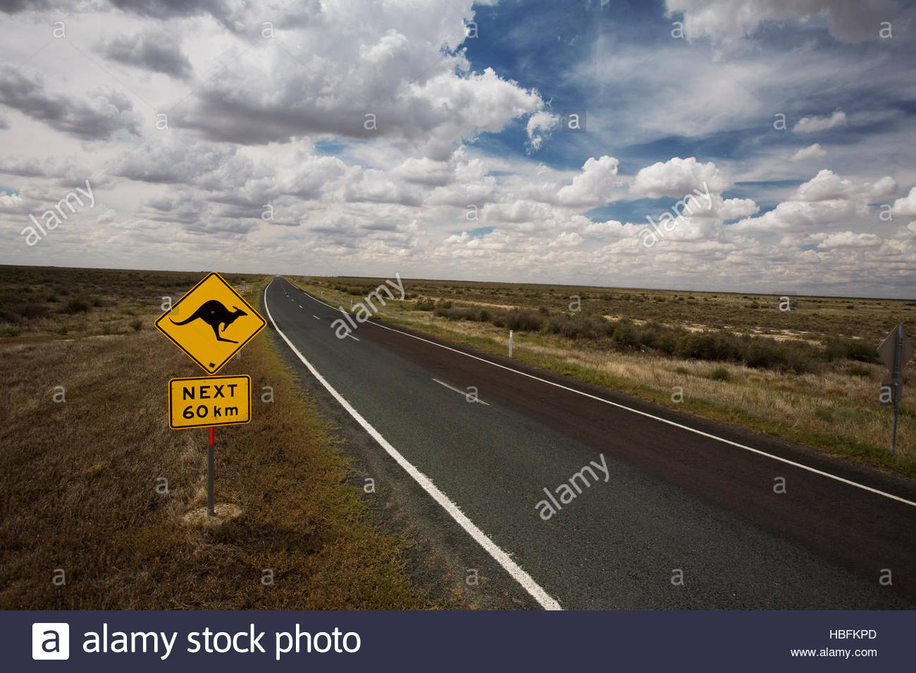 A kangaroo crossing sign on the side of a road. - Stock Image