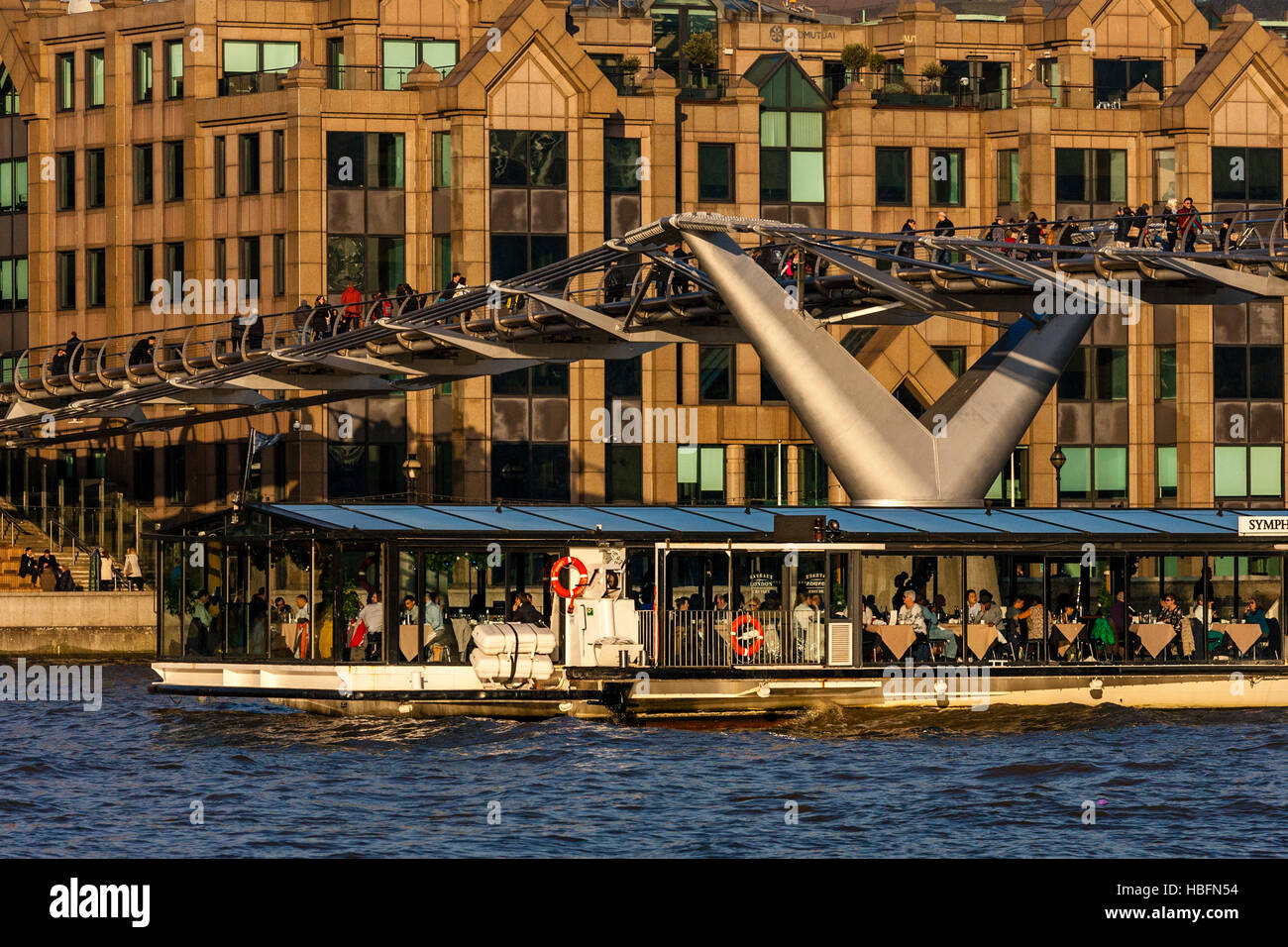 A Symphony River Cruise Boat Passes Underneath The Millennium Bridge On The River Thames, London, England - Stock Image