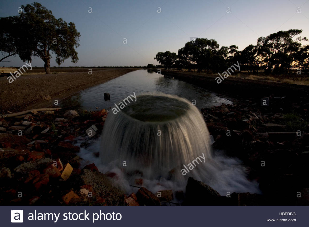 Irrigation water from the Murrumbidgee River fills a canal. - Stock Image
