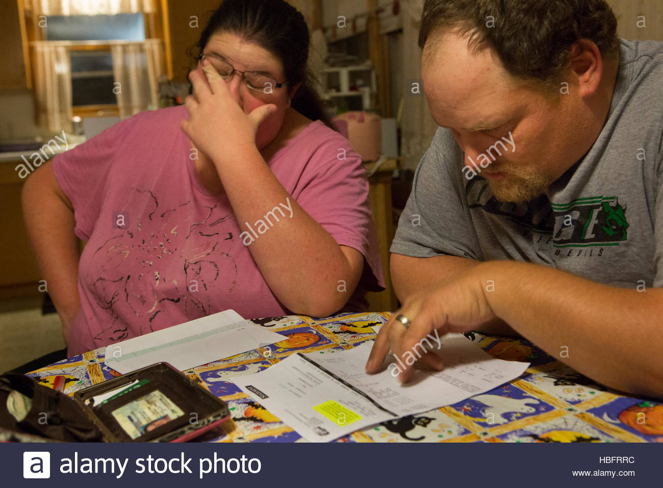 A financially struggling couple looks through overdue bills. - Stock Image