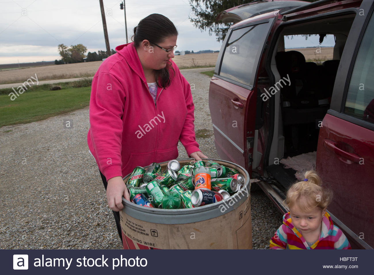 A woman recycles cans and bottles to use the money to pay bills. - Stock Image