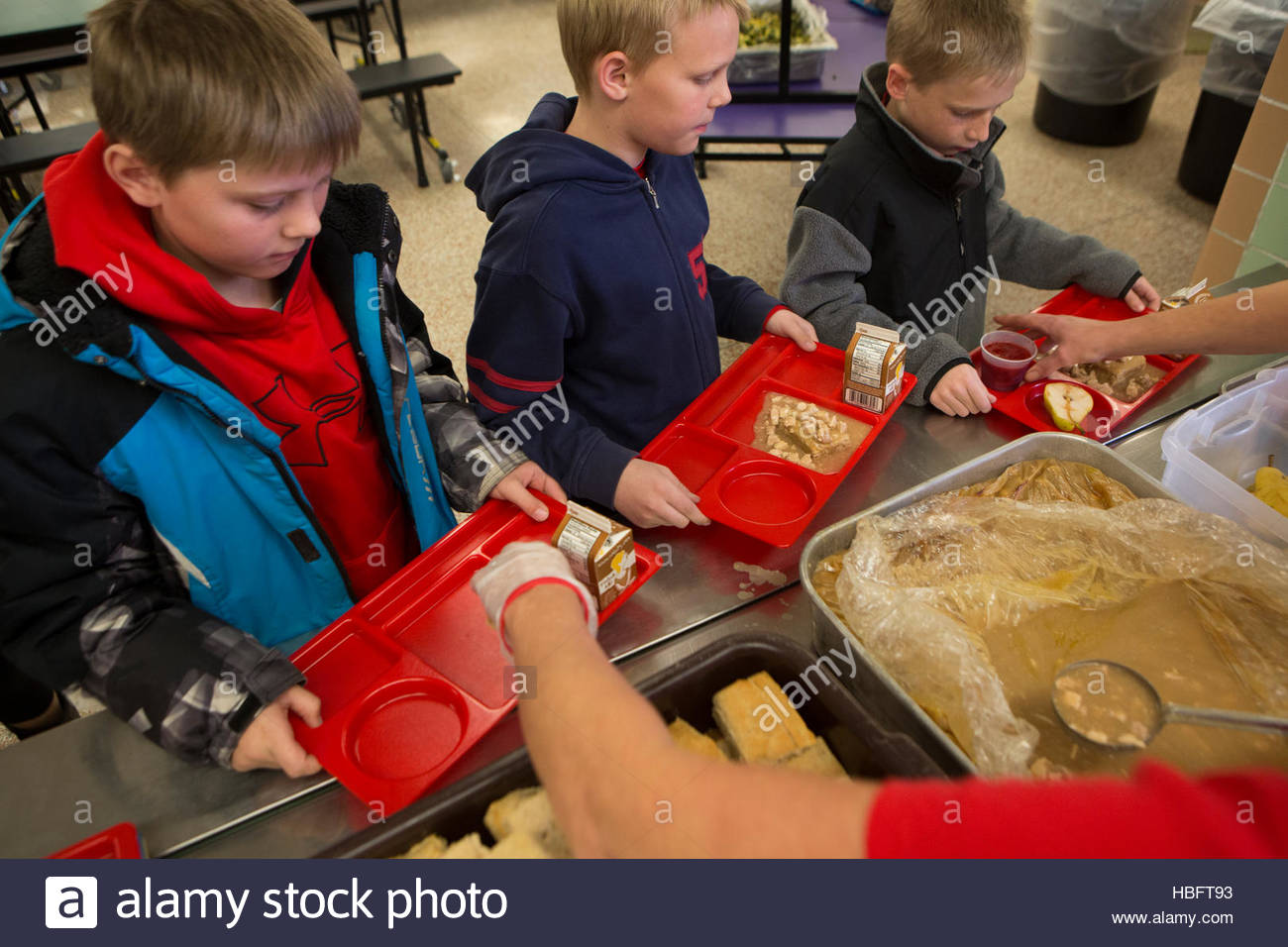 Elementary school students receive free lunch provided by the school. - Stock Image