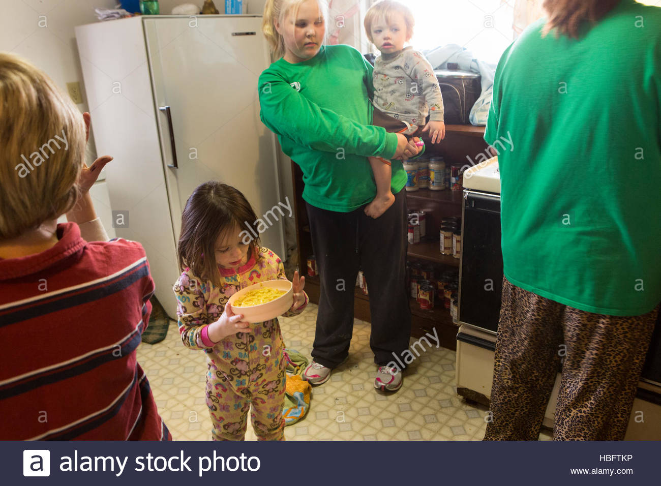 A family, classified as food insecure, eats dinner. - Stock Image