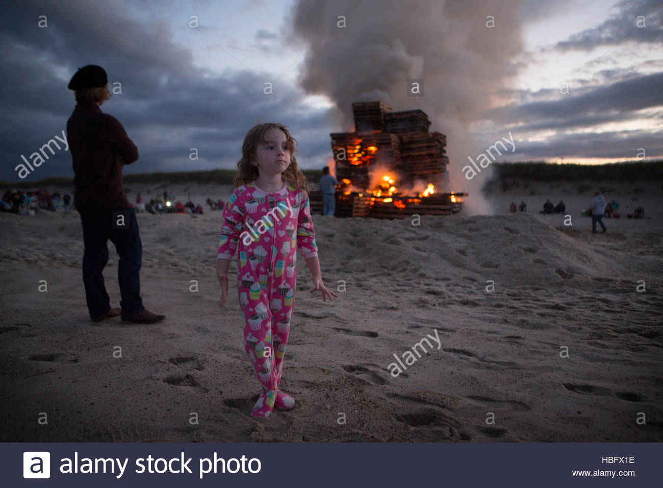 A little girl in pajamas and a huge bonfire on Nauset Beach. - Stock Image