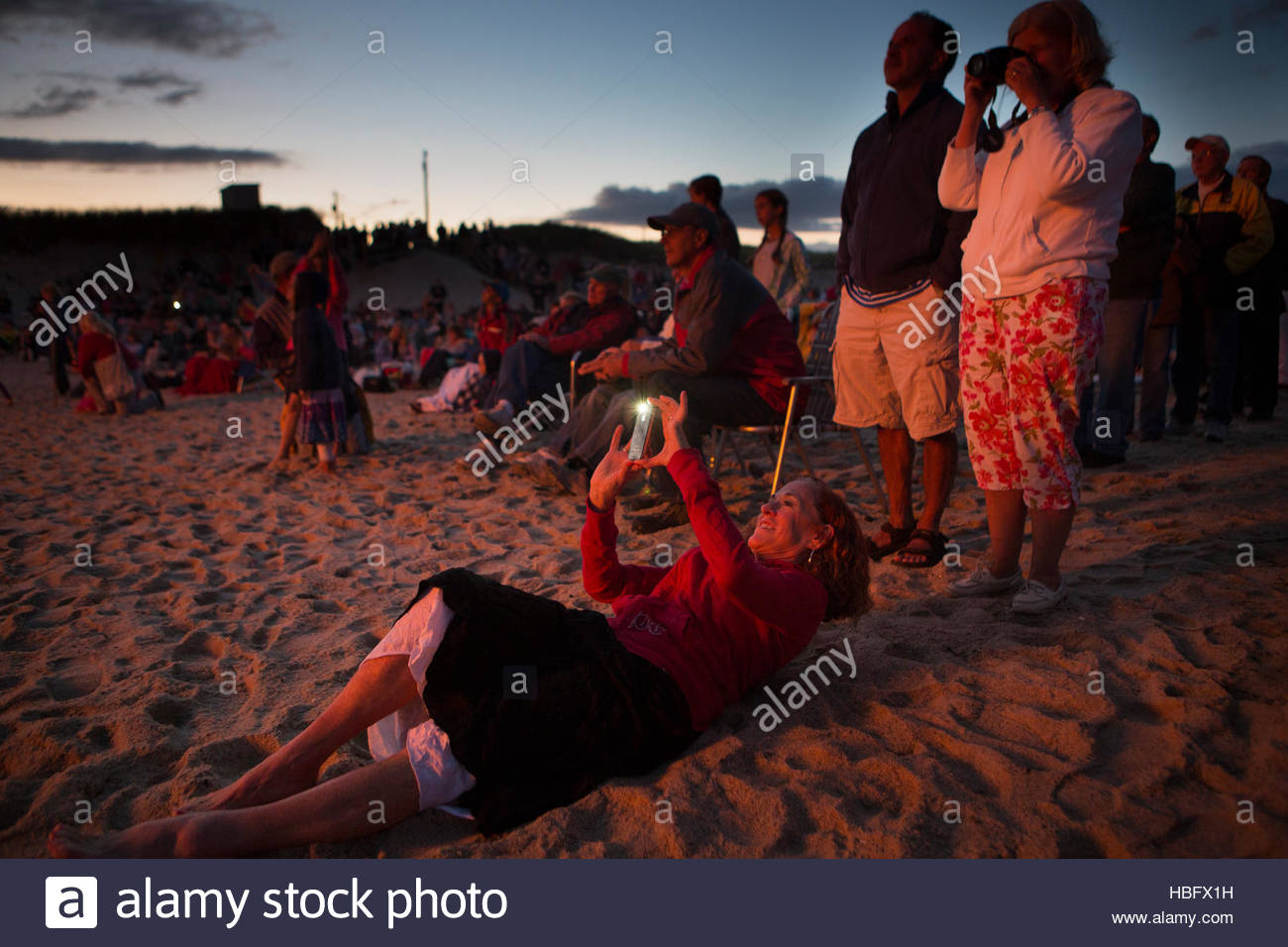 Onlookers photograph and gaze at a bonfire on Nauset Beach. - Stock Image