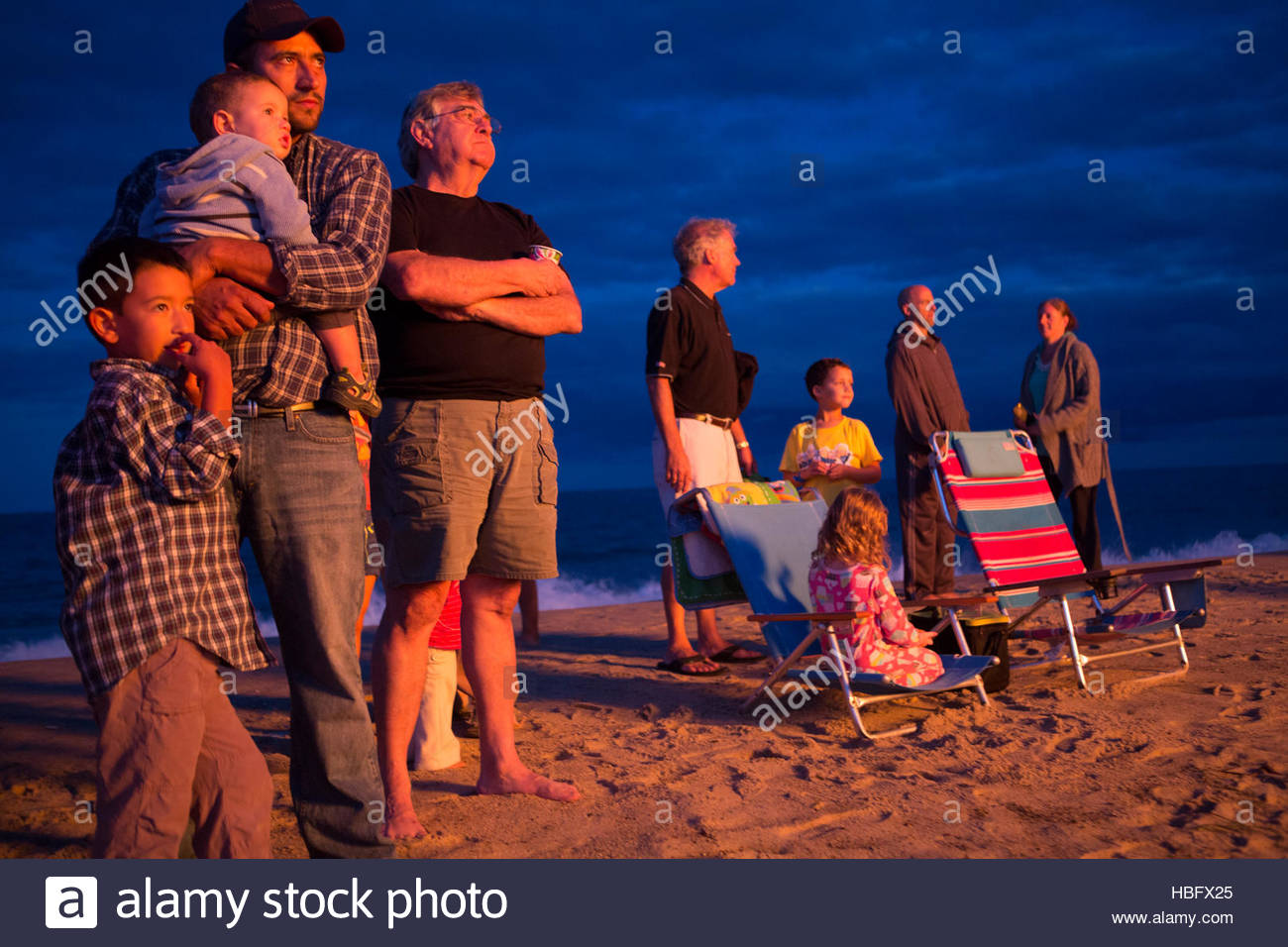 Onlookers enjoy a bonfire on Nauset Beach. - Stock Image