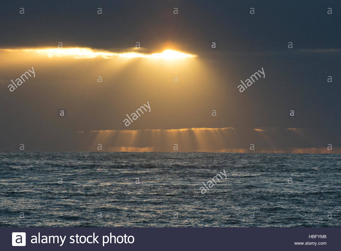 Sunlight shines through clouds above the Atlantic Ocean at Punta Norte in Argentina. - Stock Image
