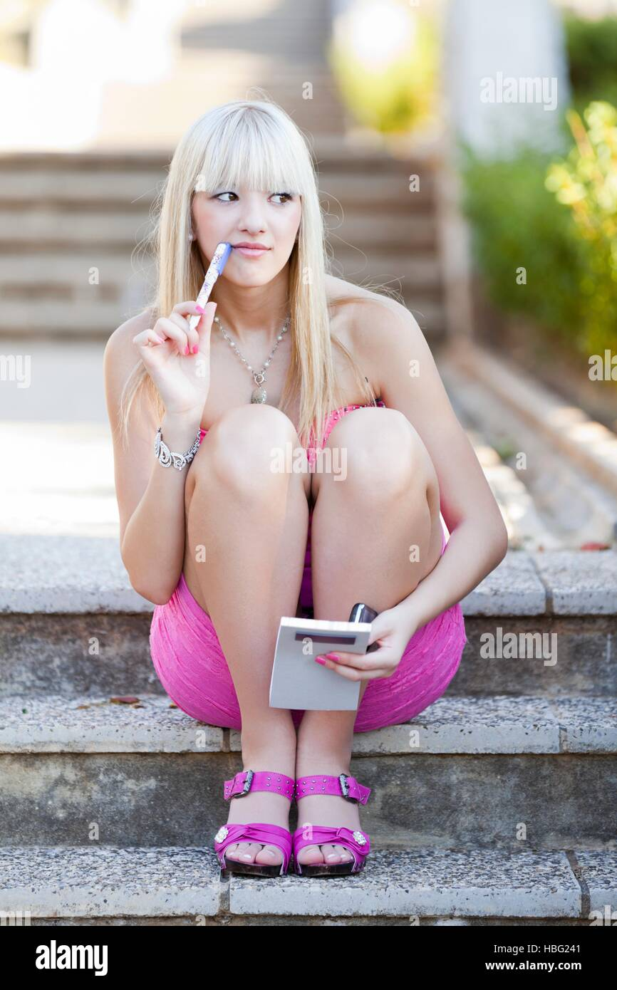Attractive young woman in pink minidress mini-dress with paper notebook pencil pen in hand student schoolgirl thinking - Stock Image