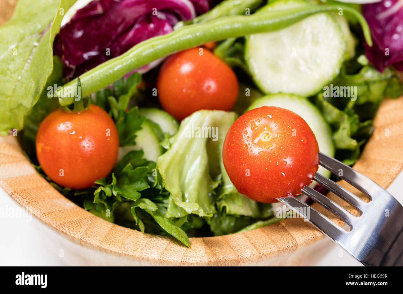 Salad with cherry tomatoes in wooden bowl Stock Photo