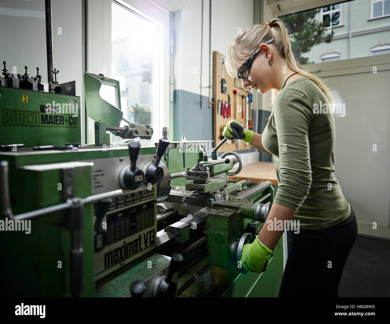 Young Woman Working On Lathe Metalwork Training Stock