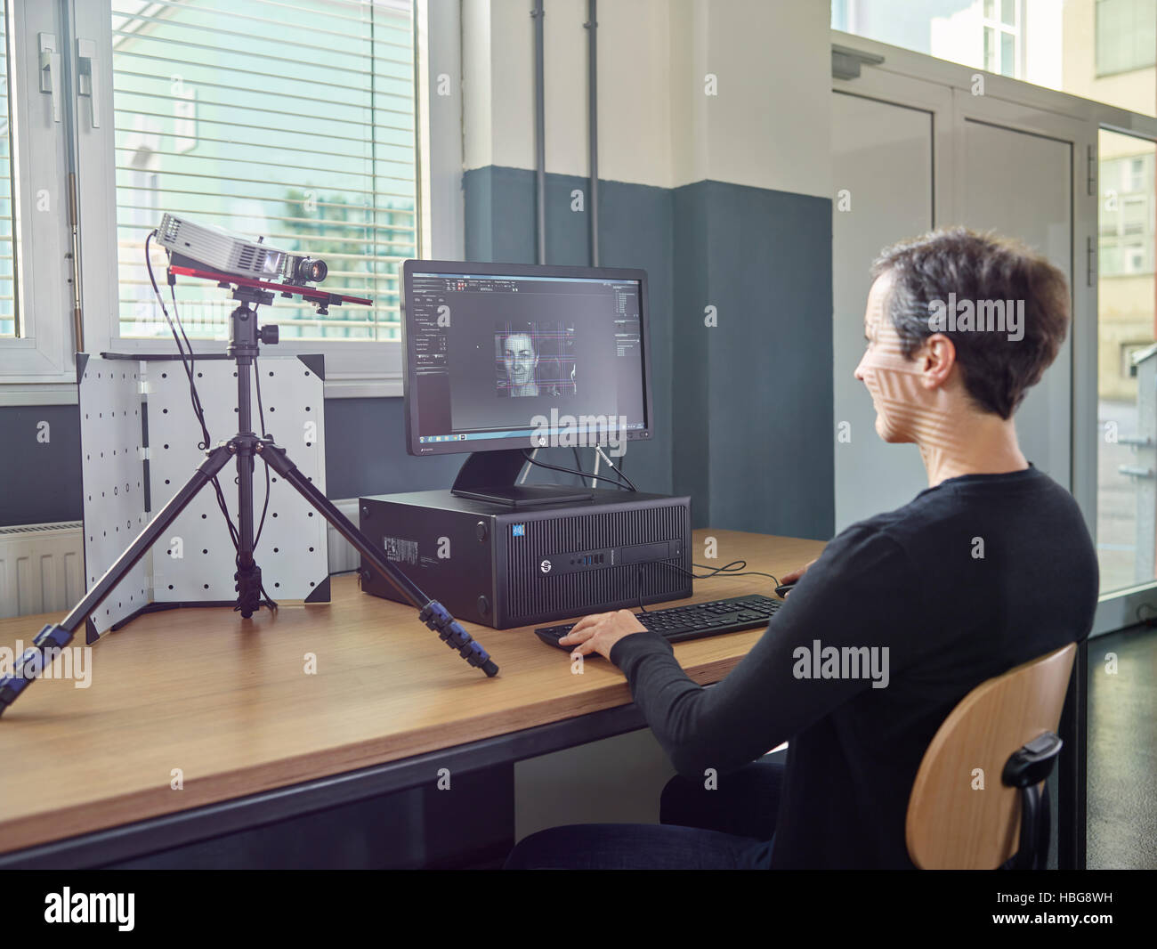 30-35 year old woman scans her head with a 3D scanner - Stock Image