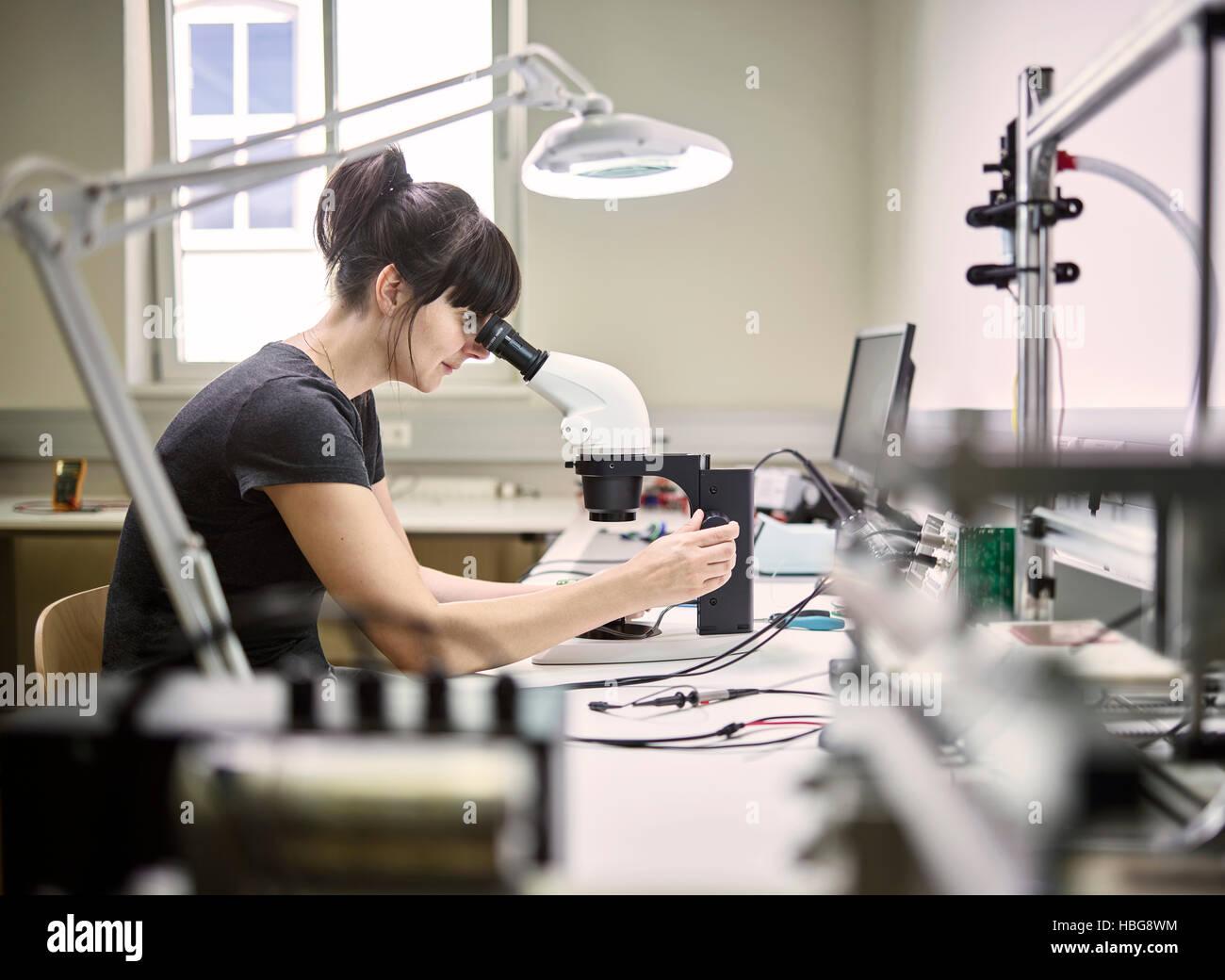 Technician, young woman using electronic microscope - Stock Image