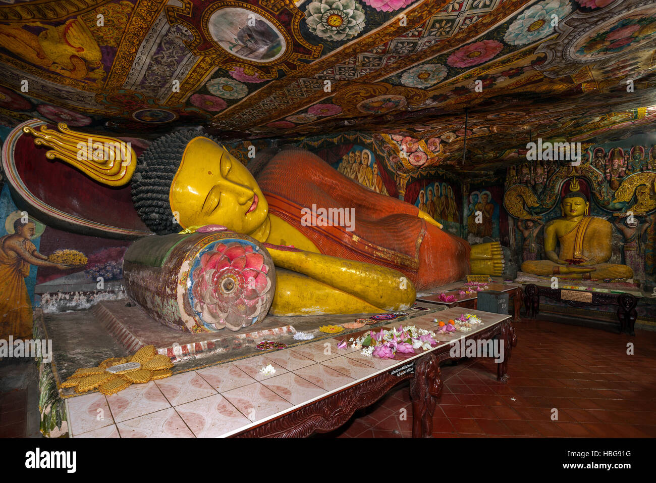Reclining Buddha statue and painted ceilings, Aluvihara Rock Cave Temple, Central Province, Sri Lanka - Stock Image