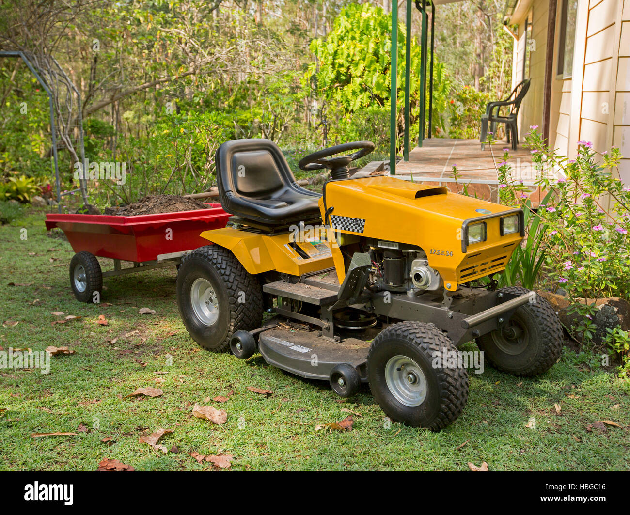 yellow ride on mower towing small red trailer full of soil. Black Bedroom Furniture Sets. Home Design Ideas