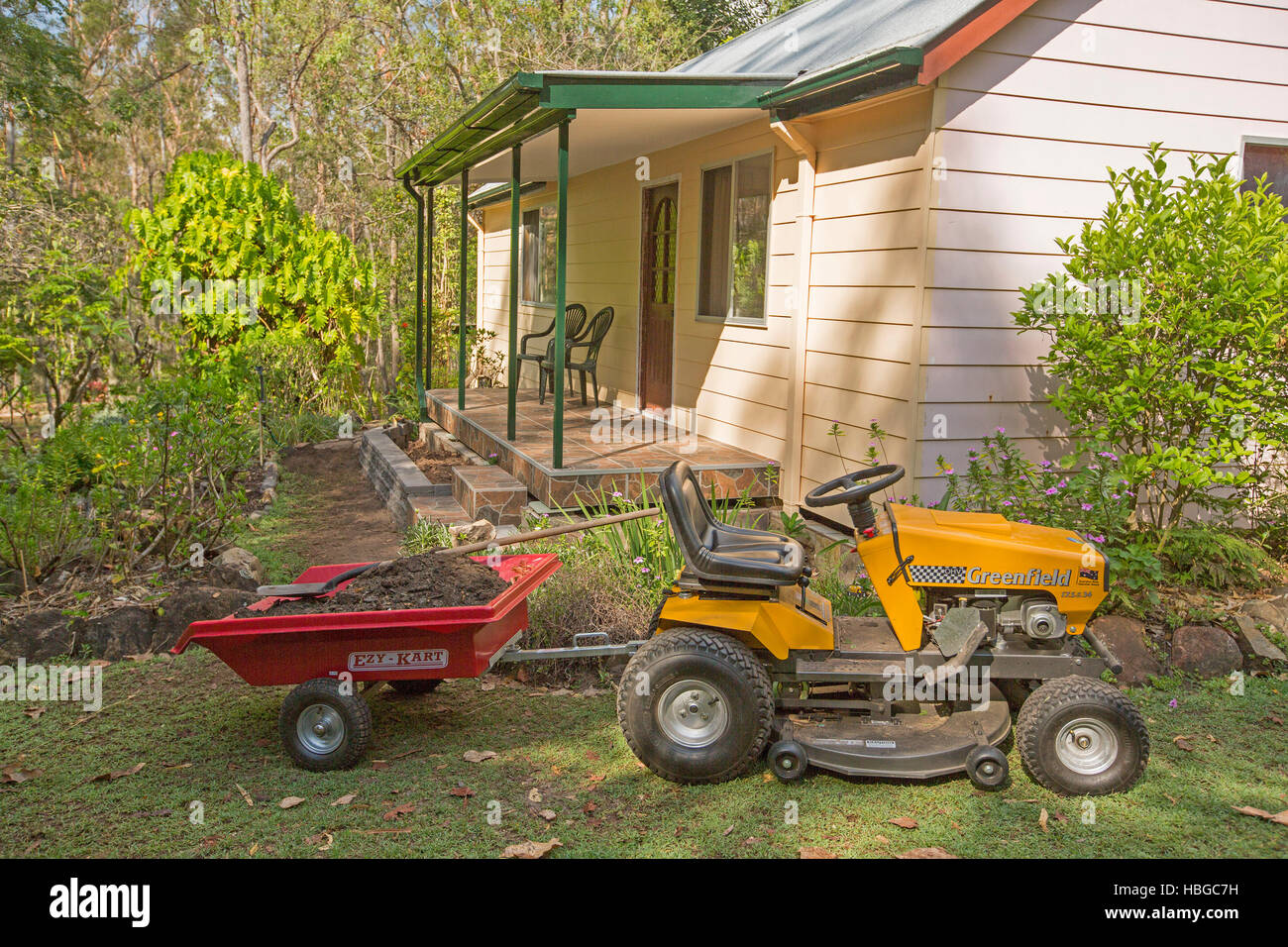 Yellow ride-on mower towing small red trailer full of soil on lawn ...