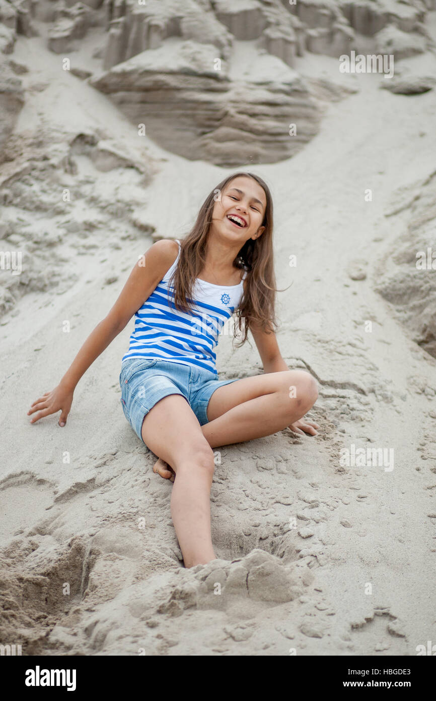 girl in a striped vest on the sand - Stock Image